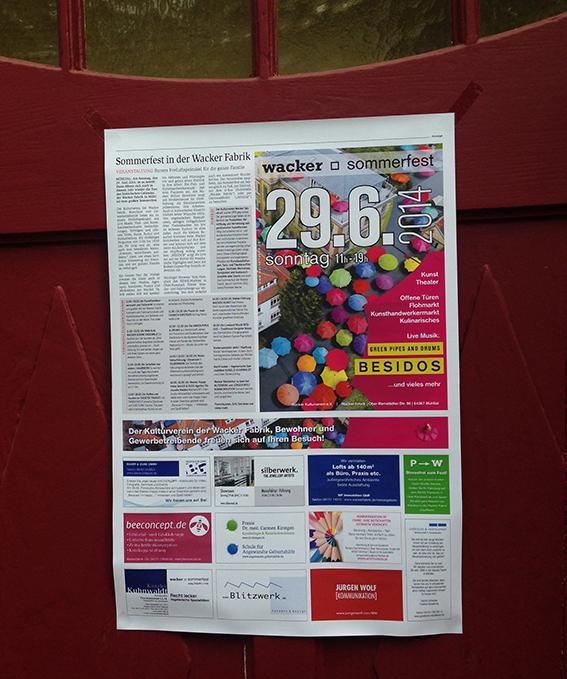 Ausdruck der Zeitungsseite zum Sommerfest auf dem roten Eingangstor in der Wackerfabrik